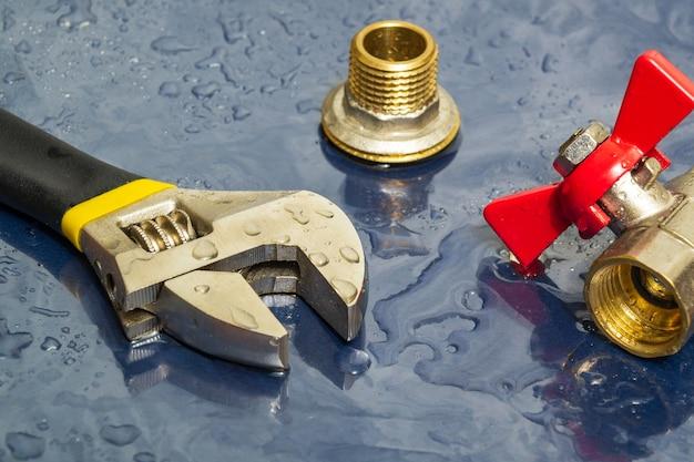 機器の修理中に水滴の配管蛇口とレンチ
