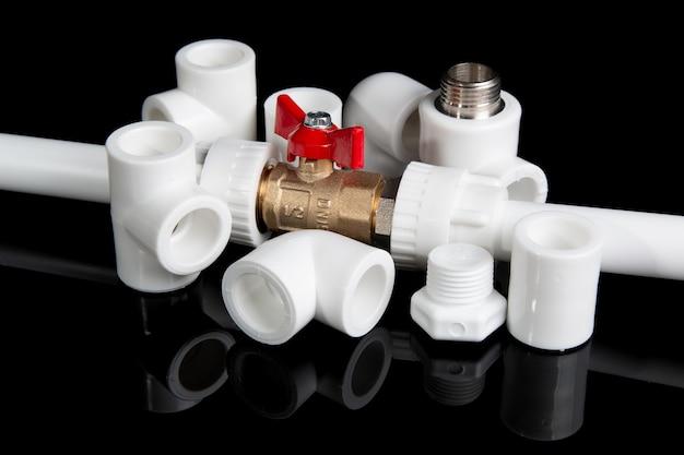 Сантехническая арматура для пластиковых труб из пвх и сантехнических ворот с шариками на черном фоне