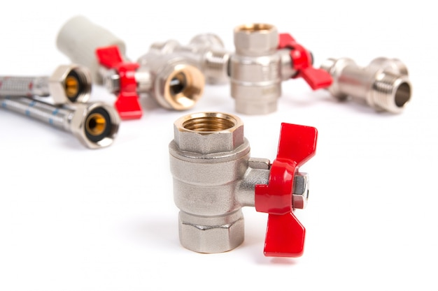 Plumbing gate ball vales, flexible water hose and fittings on a white