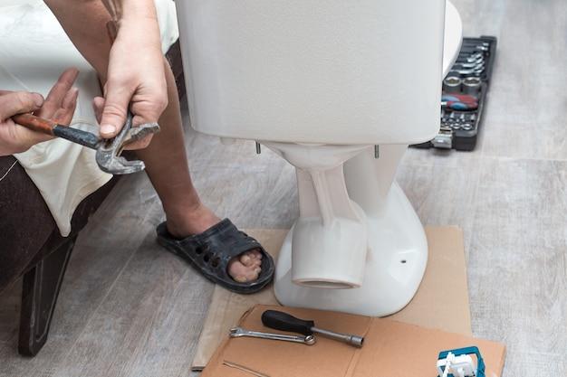배관 설치 남자는 변기에 변기 물통을 설치합니다