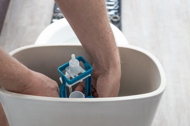 배관 설치 배관공이 변기 물탱크에 수세식 펌프를 설치합니다.