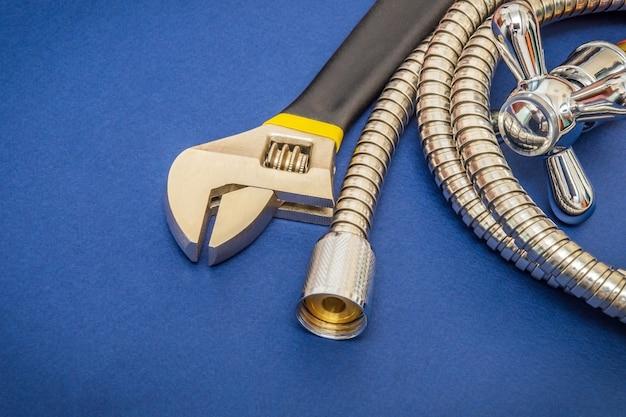 青色の背景の配管材の蛇口、ツール、ホースは、シャワーの交換に使用されます