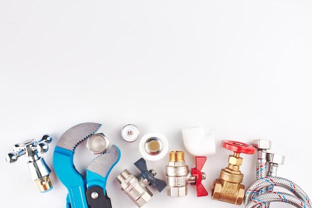 Сантехнические детали и инструменты на белом фоне