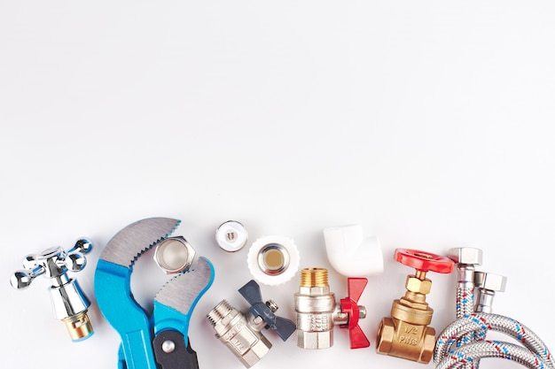 Plumbing parts and tools on a white background