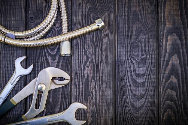 어두운 빈티지 나무 배경에 물 호스를 연결하기 위한 배관 도구와 장갑.