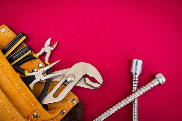 Plumbing tools in the bag on red background