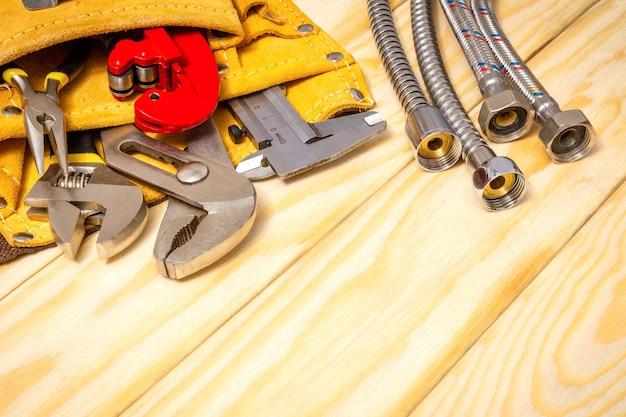Сантехнические инструменты в сумке и шланги на деревянных досках