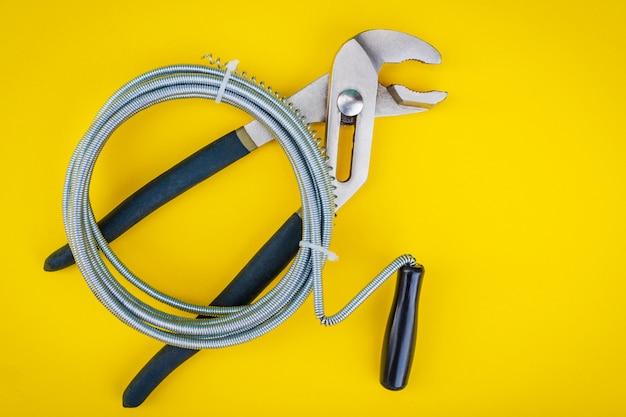 Plumbing tools on yellow background