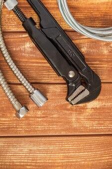 Сантехнический ключ и шланг на старинных деревянных досках