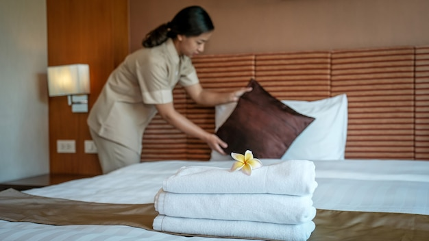 ホテルのメイドの前にあるプルメリアとタオルが、高級ホテルの部屋のベッドを観光旅行の準備にしています。
