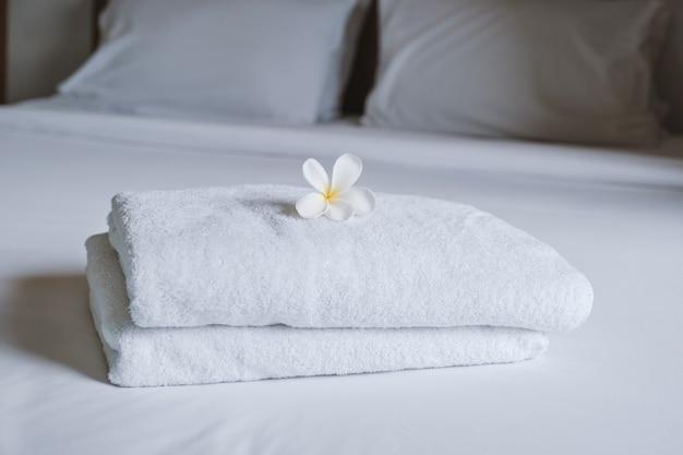 Плюмерия и полотенца на кровати в роскошном гостиничном номере готовы к туристическому путешествию.