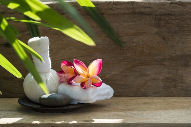 Plumeria flower and massage ball spa aromatherapy products on wood
