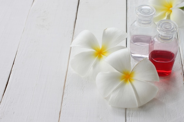 Plumeria and gel bottle is placed on a white wooden floor.