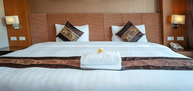 Plumeria and towels on the bed in the luxury hotel room ready for tourist travel.
