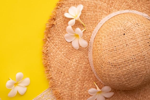Цветок plumeria и деревянная шляпа на желтой предпосылке.
