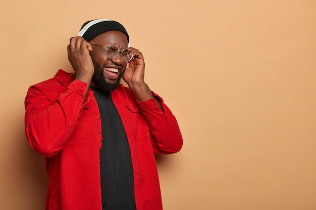 Plump black man stands half turned against beige wall, listens audio track, enjoys loud sound in headset, laughs and shows white teeth