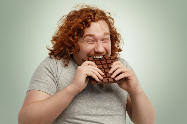 Plump funny redhead young caucasian male with curly hair biting large of chocolate