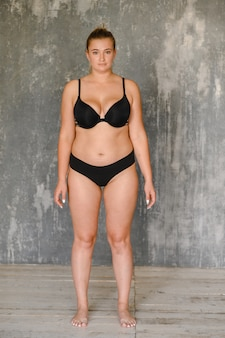A plump girl in a swimsuit stands near the wall. body positive. size plus