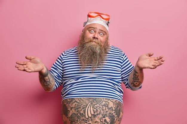 Uomo adulto barbuto grassoccio esitante allarga le mani con dubbio, indossa attrezzatura per lo snorkeling, ha una folta barba, vestito con una camicia da marinaio non dimensionata