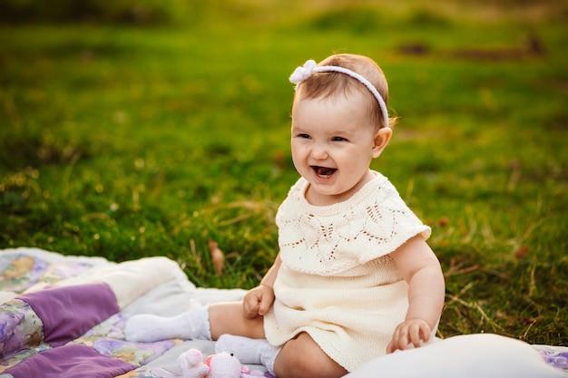 Plump little girl sits on white blanket