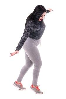スポーティな形のふっくらとした女性が想像上のロープで靴下の上を歩く