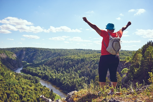 The plump woman raised her hands up, rejoicing ascent to the mountain. the concept of victory over oneself, motivation, strength of character. a beautiful bird's-eye view of a mountain river