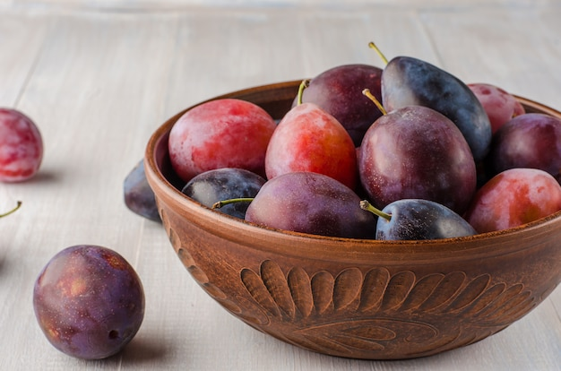 Plums of different varieties on a light wooden background.