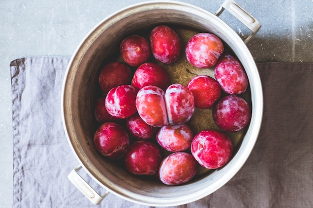 Plums of different varieties in an old metal saucepan. gray concrete background, gray text