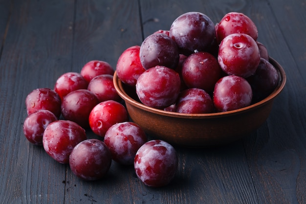 Plums in dish on dark wooden table