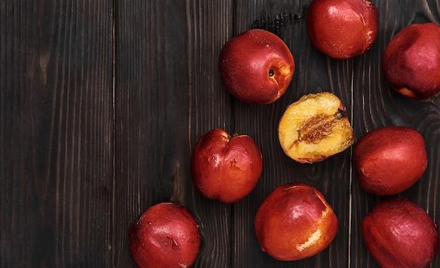 暗い素朴なテーブルの上のプラム、熟したフルーツのレイアウト。コピースペースのある熟したプラムの上面図。フルーツワインやパイジャムの材料のアイデア。農業、ガーデニング、収穫の概念。