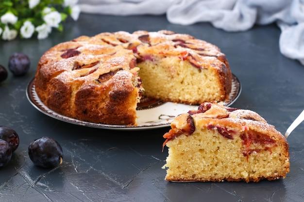 プラムパイは暗い背景のプレートにあり、前景にはケーキがあり、新鮮なプラムはテーブルの上にあります