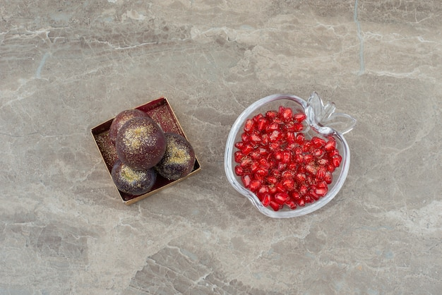 Plums in small box decorated with glitter and pomegranate seeds.