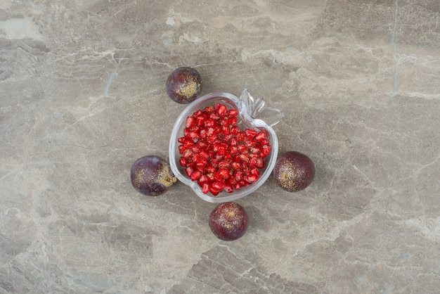 Plums with glitter and pomegranate seeds on marble.