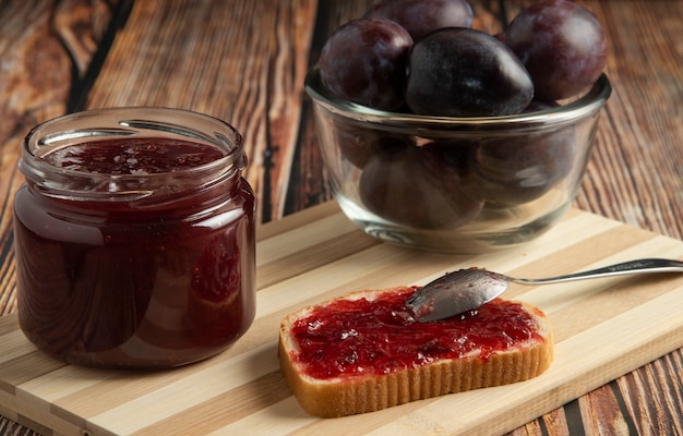 Plums with a jar of confiture and a toast bread.