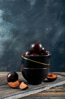 Plums with slices with wooden board in a multiple bowls on dark wooden and grey grunge background, side view.