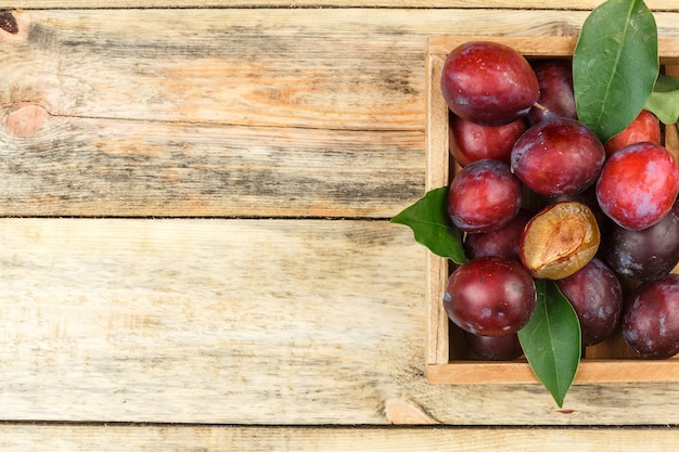 Plums in a wooden crate on a wooden board background. top view. free space for your text