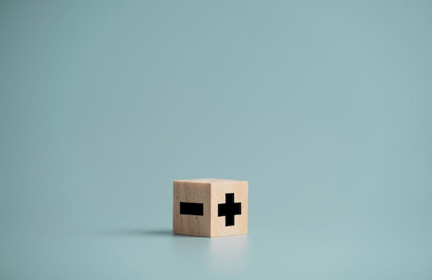 더하기와 빼기 기호는 나무 큐브 블록에 화면을 인쇄하고 공간을 복사하는 반대편에 긍정적 인 사고 방식 선택 개념입니다.