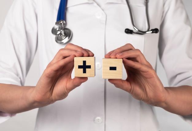 나무 큐브에 더하기 및 빼기 기호. 의료 개념.