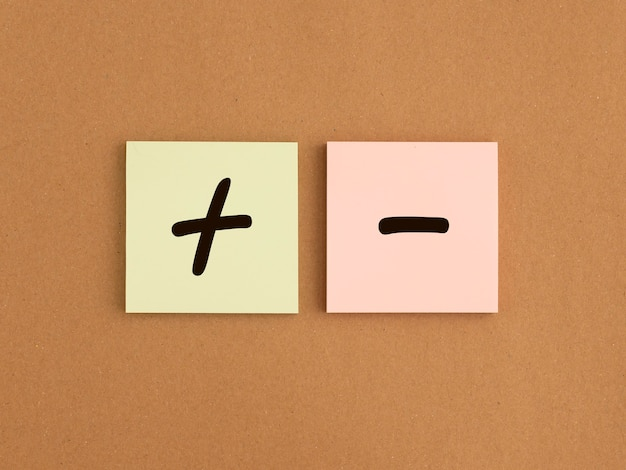 Plus and minus signs on papers concept of positive and negative pros and cons good vs bad comparison...