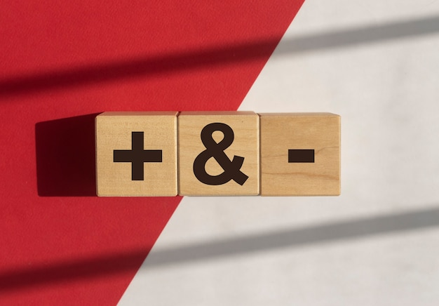 Plus and minus signs on wooden dices on white and red background with daylight concept of positive a...