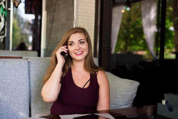 プラスサイズの美しい若い女性タブレットと電話でレストランで。