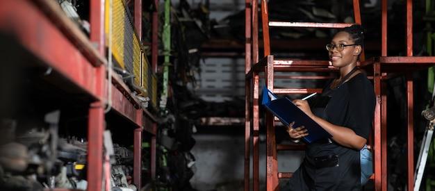 Черная женщина-работница большого размера осматривает запас старых автомобильных запчастей во время работы на большом автомобильном складе