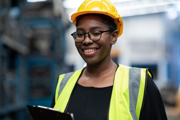 Черная женщина-работница большого размера в защитном шлеме с каской осматривает запас старых автомобильных запчастей во время работы на большом автомобильном складе