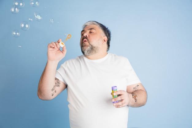 Modello maschile di dimensioni più grandi facendo bolle isolate sulla parete dello studio