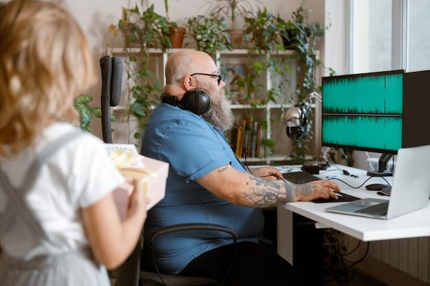 헤드폰을 끼고 컴퓨터 작업을 하는 플러스 사이즈 남자, 방에 선물 상자를 들고 있는 여자