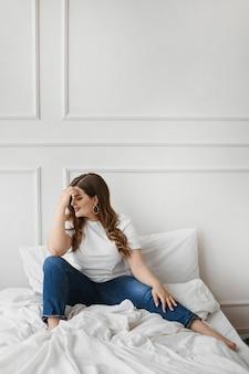 Девушка модели больших размеров в джинсах и пустой белой футболке сидит на кровати. xxl мода. неидеальная красота