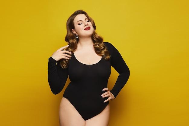 노란색 배경에서 포즈를 취하는 검은 bodysuit에서 밝은 화장과 플러스 사이즈 모델 소녀. 노란색 배경에 고립 된 검은 bodysuits에 젊은 더하기 크기 여자