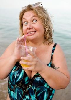 Plus sizemodel holding an orange juice