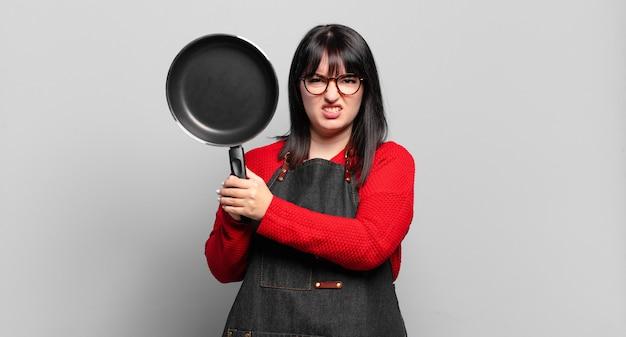 플러스 크기 예쁜 요리사 여자 냄비 요리