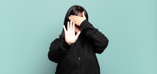 플러스 사이즈 예쁜 여자가 손으로 얼굴을 가리고 다른 손을 앞으로 올려 카메라를 멈추고 사진이나 사진을 거부합니다.